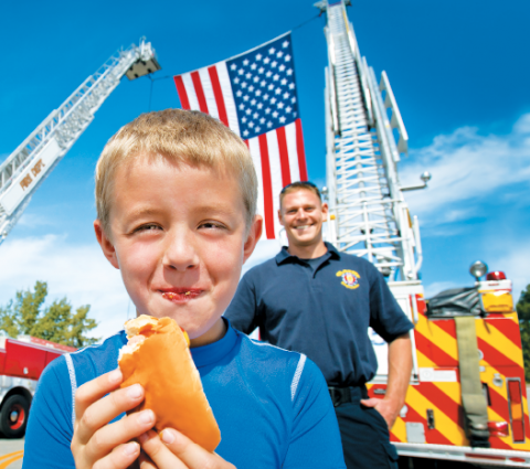 Small boy eating a hotdog and standing in front of a firetruck and firefighter