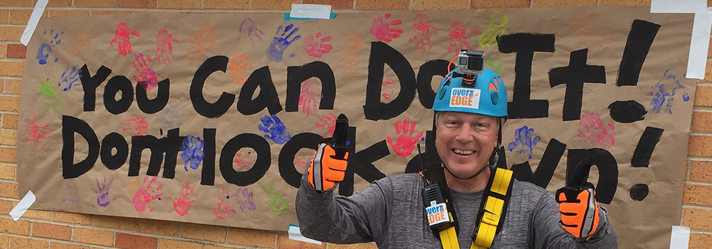 """David Gates standing in front of a banner that says """"You Can Do It. Don't Look Down"""" before he starts rappelling."""