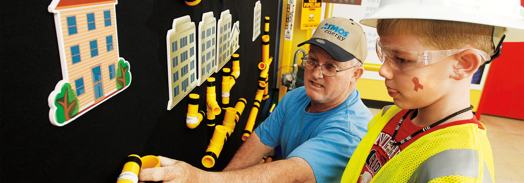 Atmos Energy employee helping a child dressed in safety gear attaching pieces of yellow pipe on a felt board that hangs on the wall.