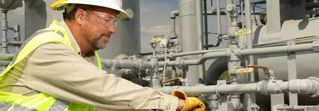 Utility worker wearing safety glasses working on a natural gas pipeline.