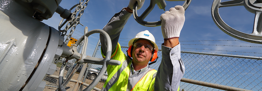 Atmos Energy employee with noise canceling headphones turning a natural gas valve on a large pipeline.
