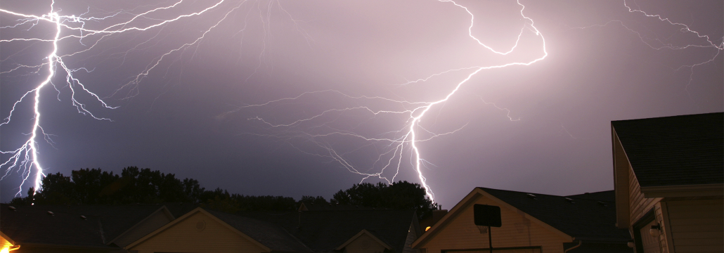 Several lightning strikes with a dark, stormy background above a neighborhood.