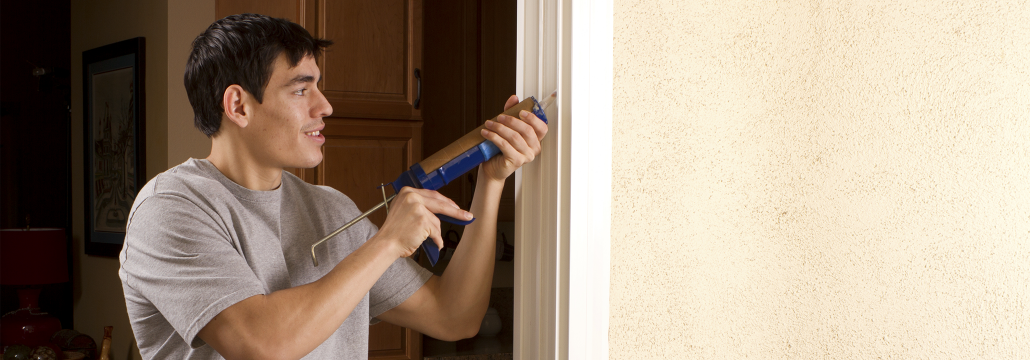 Young man caulking windows to help make his home more energy efficient.