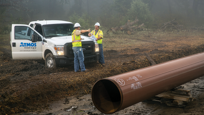 Atmos Energy truck parked outside in a muddy field with two service technicians pointing to a large pipeline