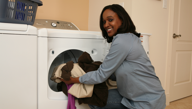 Woman putting towels into a natural gas dryer