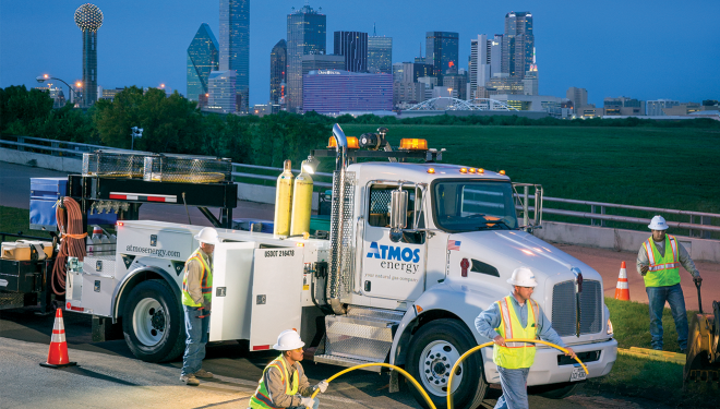 Employees working at dusk installing natural gas pipe with the background of Dallas skyline