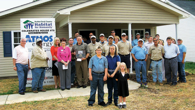 Employees standing in front of a newly constructed Habitat for Humanity with the recipients - a mother and her two young children.