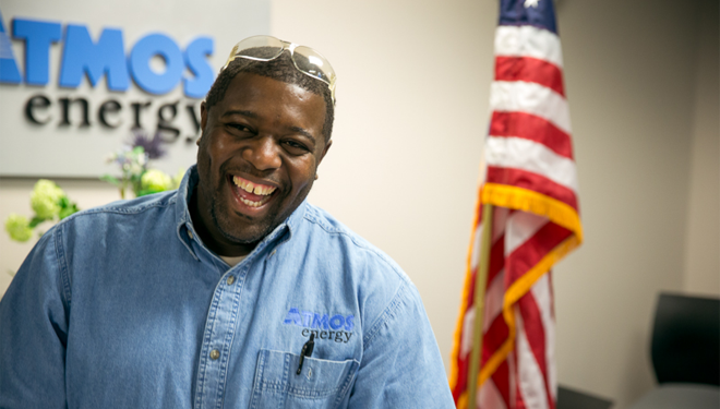 Veteran employee standing in front of the Atmos Energy logo with an American flag to his right.